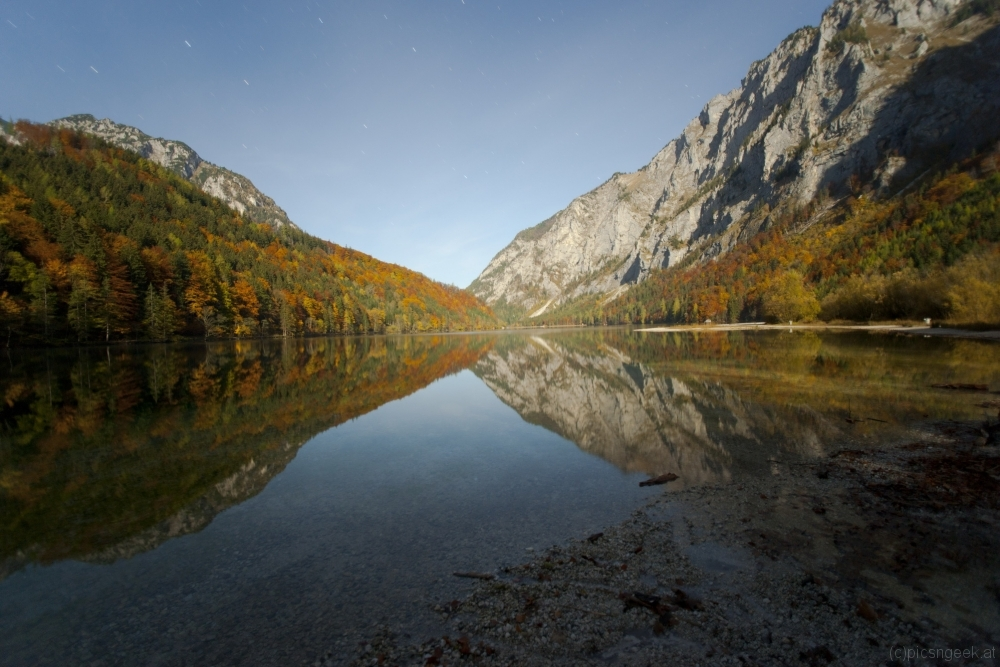 Reflections in Leopoldsteinersee in autumn moonlight with stars